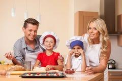 烹调与孩子一起的年轻父母 免版税库存照片