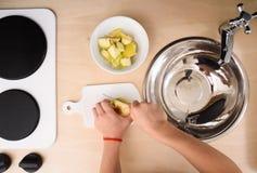 烹调与孩子 孩子在玩具厨房里切苹果之间 免版税库存图片