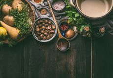烹调与成份和厨房工具的栗子汤准备在黑暗的木背景 免版税库存照片