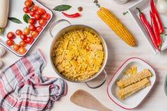 烹调与成份的玉米准备与罐和耳朵在白色木厨房背景 图库摄影