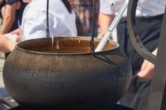 烹调与搅动一个老金属罐的一条黑围裙 免版税库存图片