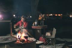 烹调与火木头和braai设备的妇女在夜之前 帐篷和椅子在前景 冒险在非洲国家公园 免版税库存照片