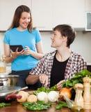 烹调与电子书在厨房里 免版税库存照片