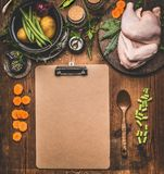 烹调与空的纸板剪贴板整鸡的鸡肉菜肴食谱背景与各种各样的健康烹调成份: 库存照片