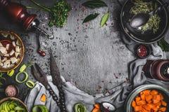 烹调与素食成份和工具,顶视图,框架的土气食物厨房用桌背景 免版税库存照片