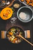 烹调与罐的准备素食南瓜意大利煨饭和匙子在黑暗的土气厨房用桌背景与烹调ingredi 免版税库存照片