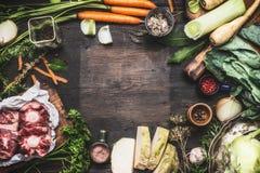 烹调与菜和肉的汤或汤的各种各样的新鲜的有机成份在黑暗的木背景,顶视图 免版税图库摄影