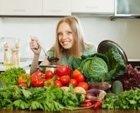 烹调与菜堆的愉快的长发妇女  免版税图库摄影