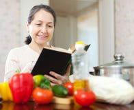 烹调与菜谱的成熟妇女 免版税库存图片