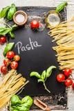 烹调与黑板、蕃茄、蓬蒿和橄榄油,顶视图的面团背景 免版税库存照片