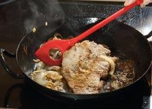 烹调与洋葱圈的牛肉 免版税库存照片