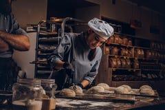 烹调主要类在面包店 有他的显示焙烧试验的准备好样品助理的厨师在厨房 库存照片