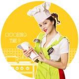 烹调书的有吸引力的主妇读书在厨房屋子 免版税库存图片