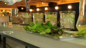 烹调从黄瓜、薄菏、柠檬汁、冰和矿泉水的五个鸡尾酒的过程,男服务员采取a 股票视频