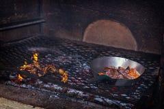 烹调传统鸡爪和遇见在煤炭格栅的香肠在非洲reastaurant 免版税库存图片