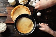 烹调俄国薄煎饼的妇女在厨房里, 免版税库存图片