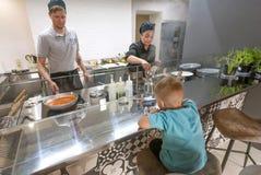 烹调做小男孩的厨师和kitchener食物在现代餐馆露天场所厨房  免版税库存照片