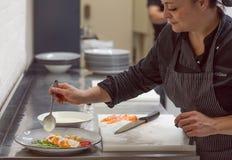 烹调做意大利海鲜carpaccio的厨师在现代餐馆厨房  免版税库存图片
