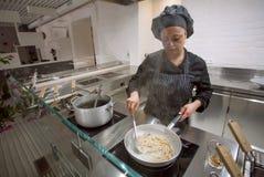 烹调做意大利食物面团或意粉的厨师在现代餐馆里面的开放厨房 免版税库存照片