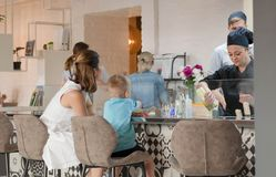 烹调做食物的厨师在孩子和家庭的开放厨房在现代餐馆里面 免版税库存图片