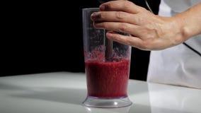烹调健康早餐,莓的妇女混合入水果鸡尾酒的搅拌器 股票录像