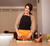 烹调健康沙拉的年轻微笑的妇女 免版税库存图片