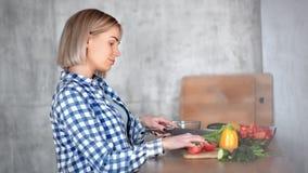 烹调健康食品的宜人的愉快的年轻主妇切开菜使用刀子侧视图 股票视频