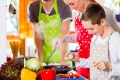 烹调健康食物的家庭在国内厨房里 图库摄影