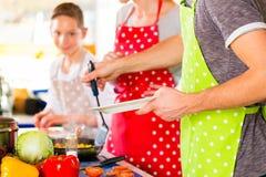 烹调健康食物的家庭在国内厨房里 免版税库存图片