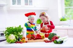 烹调健康素食午餐的孩子 库存图片