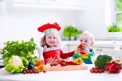烹调健康素食午餐的孩子 库存照片
