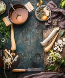 烹调准备用欧洲防风草和韭葱的蔬菜汤在土气厨房用桌背景与成份,罐,菜bro 免版税库存照片