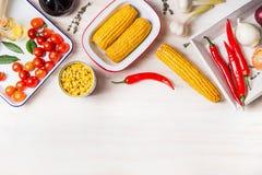烹调准备用玉米穗、罐装和煮熟的玉米和成份蔬菜菜肴的在白色木厨房用桌ba 图库摄影