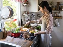 烹调午餐的妇女在厨房里 免版税库存图片