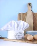 烹调厨具和厨师的帽子-垂直的现代厨房 免版税库存照片