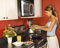 烹调厨房妇女年轻人的有吸引力的breakfas 免版税库存照片