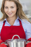 烹调厨房的年轻白肤金发的妇女女孩 库存图片