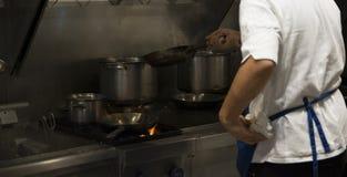 烹调可口板材的苦干者国际厨师在一家国际餐馆 库存照片