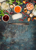 烹调各种各样的亚洲人烹调成份和调味汁与筷子在土气背景,顶视图,地方文本的 图库摄影