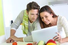 烹调和使用片剂的夫妇 免版税库存照片