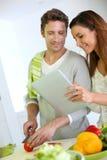 烹调和使用片剂的夫妇 库存图片
