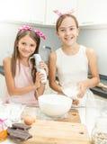 烹调和做面团的两个微笑的女孩画象  免版税库存照片