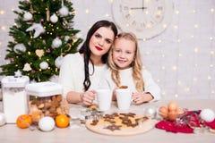 烹调和吃圣诞节曲奇饼的女孩和她的母亲 库存照片