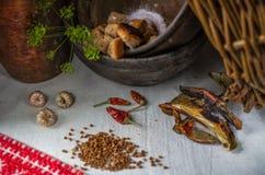 烹调土气食物的过程 干蘑菇,荞麦,大蒜,红辣椒,面包屑 厨房土气老器物 免版税库存图片