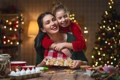 烹调圣诞节曲奇饼的家庭 免版税库存照片