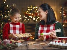 烹调圣诞节曲奇饼的家庭 免版税库存图片