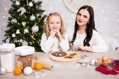 烹调圣诞节曲奇饼的母亲和女儿在厨房里 免版税库存图片