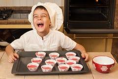 烹调圣诞节蛋糕的孩子 免版税库存图片