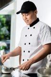 烹调在一个商业厨房里的厨师 免版税库存照片