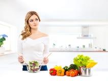烹调在一个现代厨房里的少妇 免版税库存照片